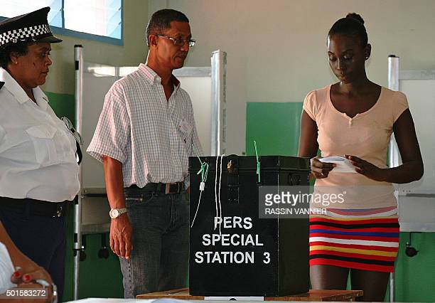 A woman casts her ballot for the presidential elections in Victoria the capital of the Indian Ocean archipelago of the Seychelles on December 16 2015...