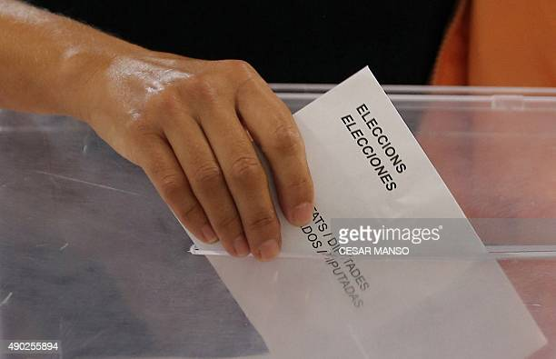 A woman casts her ballot for the regional election at a polling station in Badalona on September 27 2015 After an emotional climax to campaigning on...