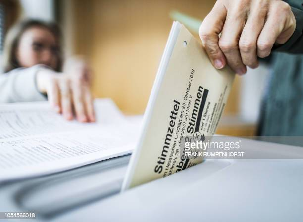 Woman casts her ballot for the state elections in Hesse at a polling station in Frankfurt on October 28, 2018. - Shifting tectonic plates in German...