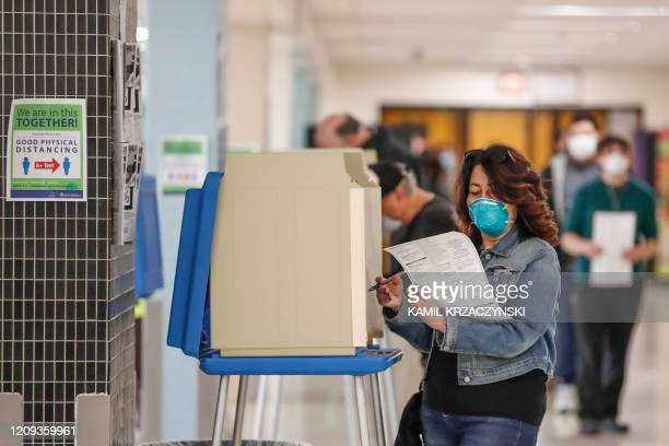 A woman casts her ballot in a Democratic presidential primary election at the Hamilton High School in Milwaukee Wisconsin on April 7 2020 Americans...