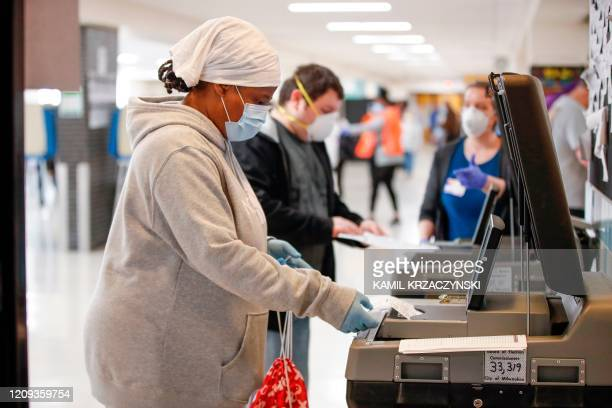 A woman casts her ballot in a presidential primary election at the Hamilton High School in Milwaukee Wisconsin on April 7 2020 Americans in Wisconsin...