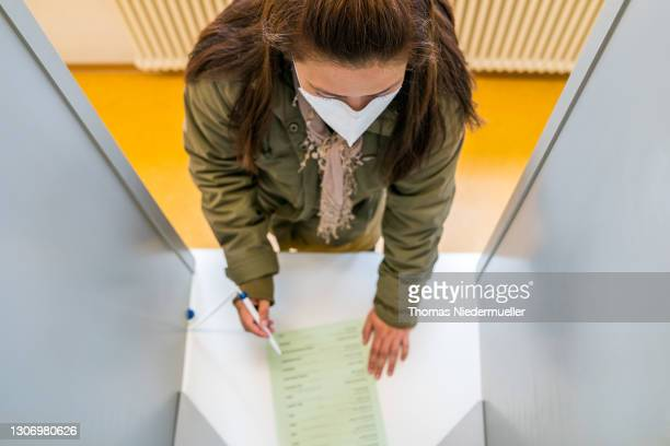 Woman casts her ballot in state elections in Baden-Wuerttemberg during the coronavirus pandemic on March 14, 2021 in Stuttgart, Germany. Voters are...
