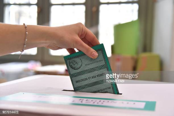 Woman casts her ballot on March 4, 2018 at a polling station in Rome. Italians vote today in one of the country's most uncertain elections, with...