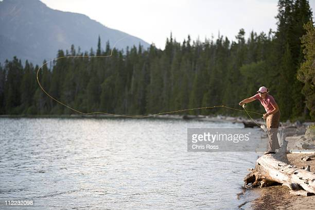 a woman casts her flyline from the shore of a lake. - jackson hole stock pictures, royalty-free photos & images
