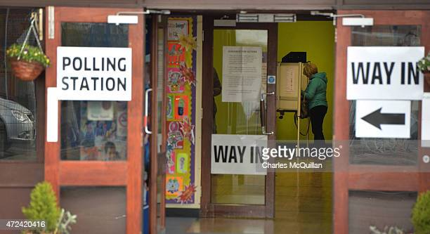 A woman casts her vote as polling gets under way at the Glen Road polling station on May 7 2015 in Belfast Northern Ireland The United Kingdom has...