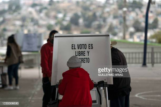 Woman casts her vote at a polling station during midterm elections in Tijuana, Mexico, on June 6, 2021. - Mexicans began voting Sunday in elections...