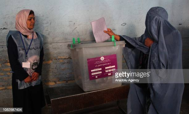 A woman casts her vote at a polling station during the parliamentary elections in Herat Afghanistan on October 20 2018