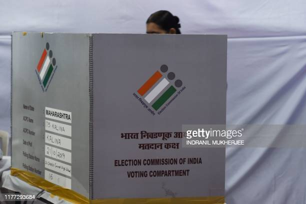 A woman casts her vote at a polling station during the State Assembly election in Mumbai on October 21 2019