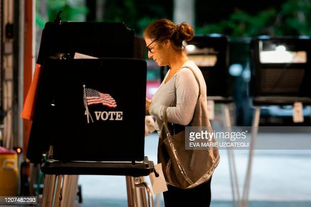 A woman casts her vote during the Florida primary election at Doris Phil Sanford Fire Rescue Station Coral Gables in Miami Florida on March 17 2020...