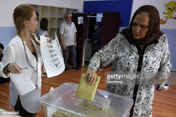 An electoral official takes sealed ballots from a box during a ballot count following voting in the parliamentary and presidential elections in...
