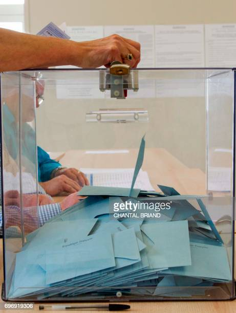 A woman casts her vote into a ballot box at a polling station in SaintPierre in the French overseas Collectivity of SaintPierre and Miquelon on June...