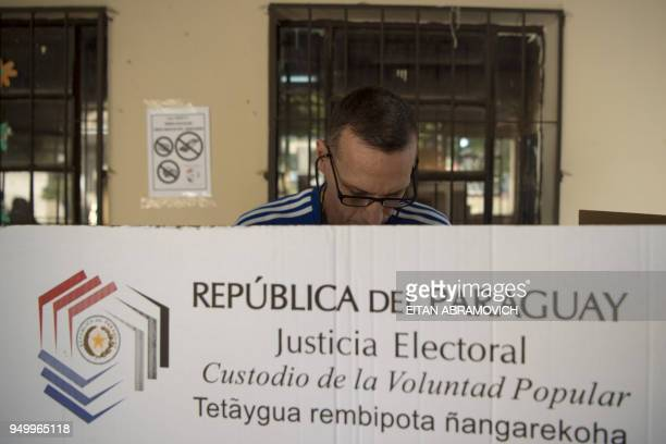 A woman casts his vote at a polling station in Mariano Roque Alonso outskirts of Asuncion on April 22 during Paraguay's presidential election Opinion...