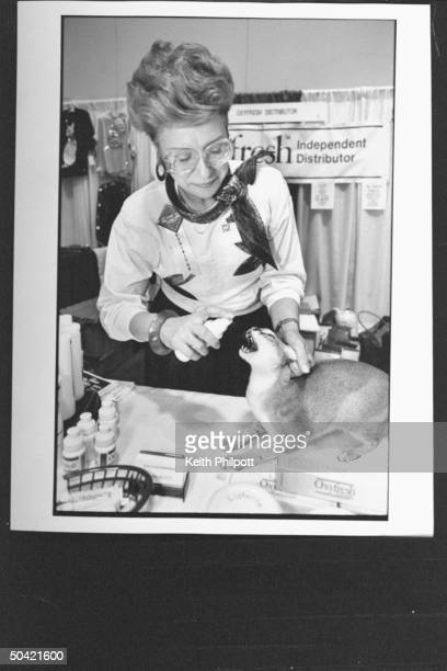 Woman cat owner plying breath freshener spray in mouth of her Abyssinian cat to get rid of food breath at the Purina Ralston and Cat Fanciers' Assn...