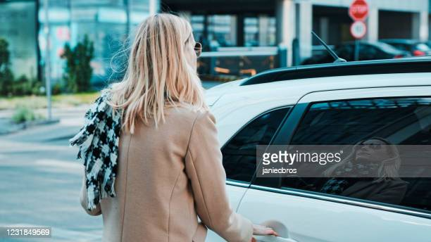 woman catching an uber in the city center. getting into car - world championship stock pictures, royalty-free photos & images
