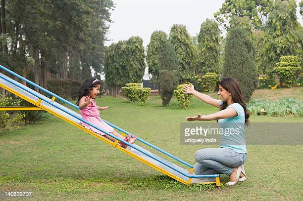woman catching her daughter at bottom of a slide - arms outstretched stock pictures, royalty-free photos & images