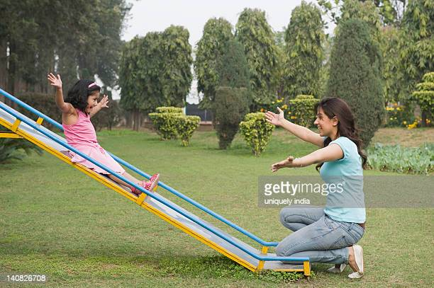 Woman catching her daughter at bottom of a slide