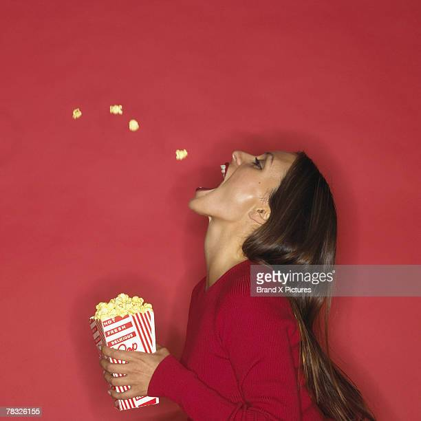 Woman catching popcorn with her mouth