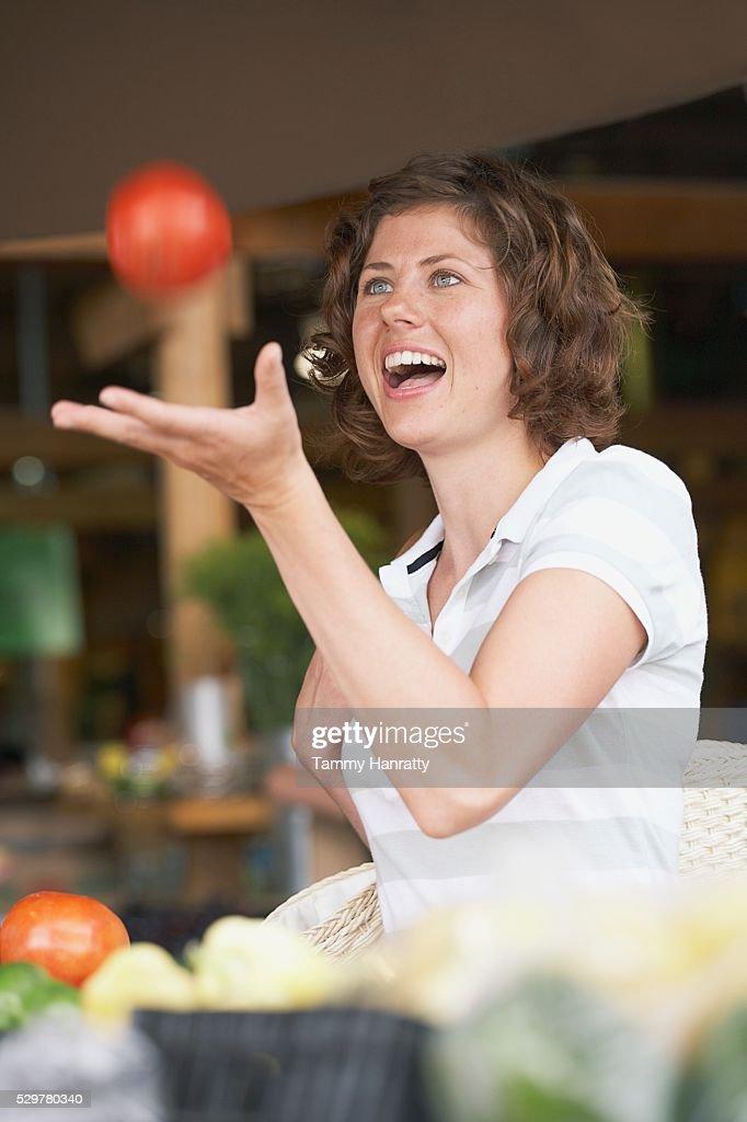 Woman catching tomato : Stock-Foto