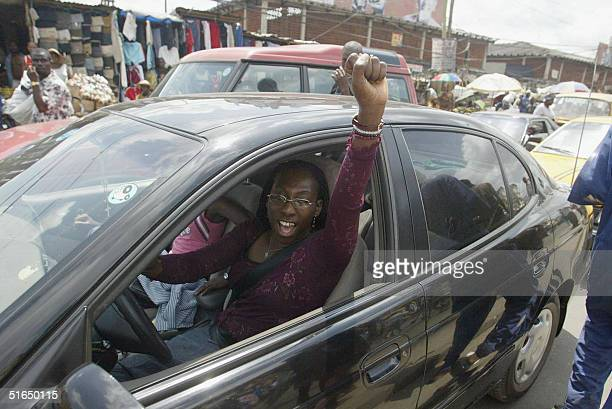 A woman caught in a traffic jam raises her fist as the president of the Nigeria Labour Congress Adams Oshiomhole arrives 03 October 2004 at a rally...