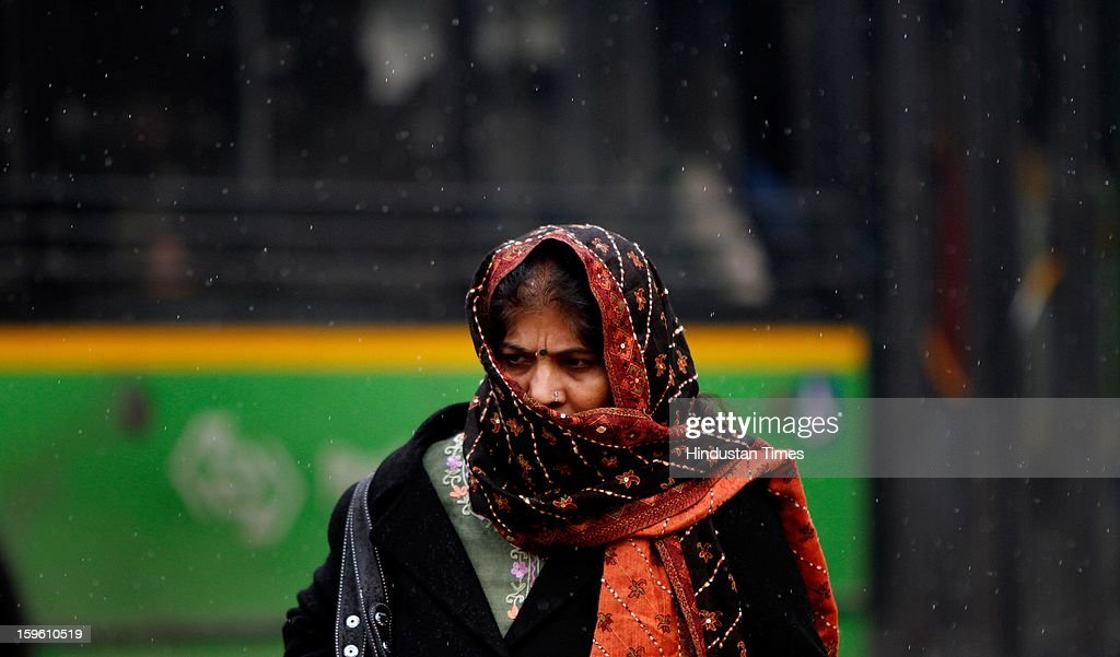 A woman caught unaware in a sudden spell of rain on a winter morning on January 17, 2013 in New Delhi, India. Capital witnessed light rain and chilly winds even though temperatures were above average.