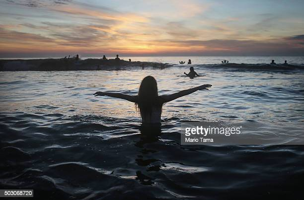A woman celebrates as revellers gather in the Atlantic Ocean for the first sunrise of 2016 near Arpoador on January 1 2016 in Rio de Janeiro Brazil...