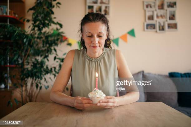 woman celebrating birthday alone at home - miljko stock pictures, royalty-free photos & images