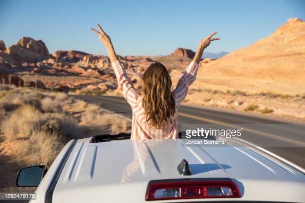 a woman celebrating out her sunroof window in the desert. - las vegas stock pictures, royalty-free photos & images