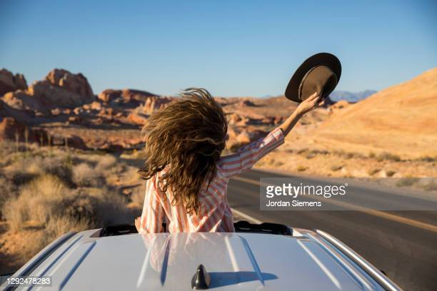 a woman celebrating out her sunroof window in the desert. - las vegas foto e immagini stock