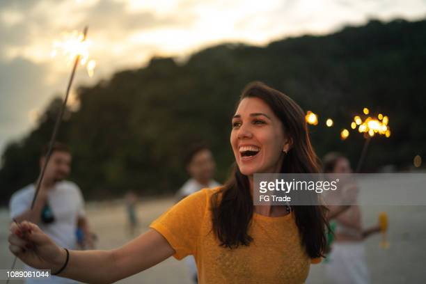 woman celebrating the new year on the beach with sparkler - luck stock pictures, royalty-free photos & images