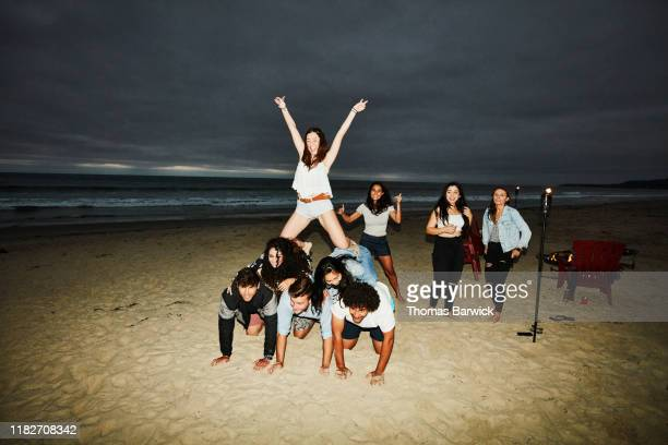 woman celebrating while making human pyramid with friends during beach party - prop stock pictures, royalty-free photos & images
