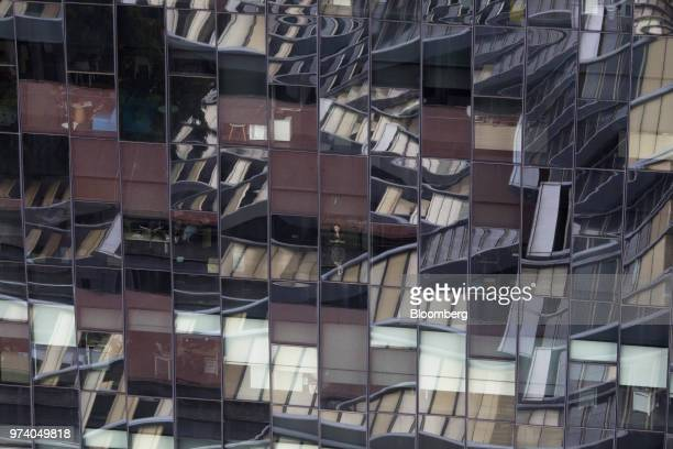A woman center stands at the window of a commercial building in Singapore on Wednesday June 13 2018 Tourism as well as the consumer sector will...