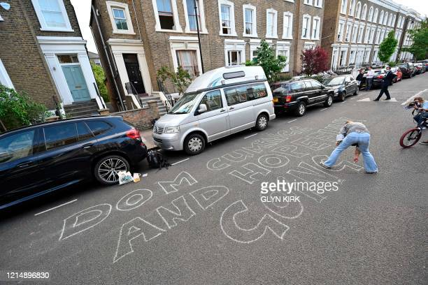 A woman chalks a message onto the road outside the home of Number 10 Downing Street special advisor Dominic Cummings in London on May 24 2020 that...