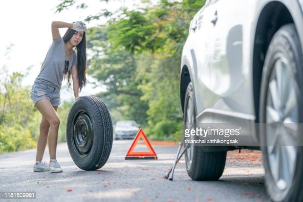 woman changing a car tire - flat tire stock pictures, royalty-free photos & images