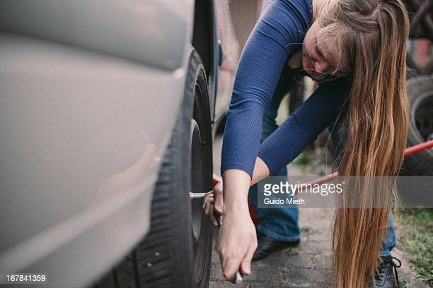 woman changing a car tire. - flat tire stock pictures, royalty-free photos & images