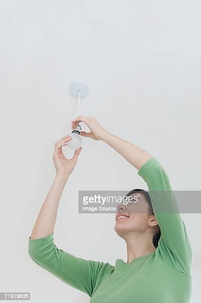 Woman changing a lightbulb