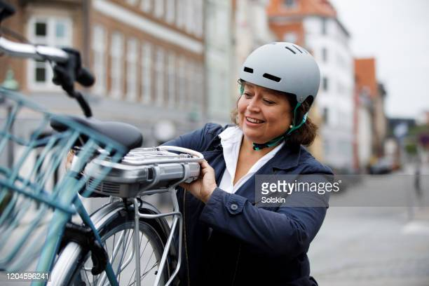 woman changing battery on electric bicycle - サイクリングヘルメット ストックフォトと画像