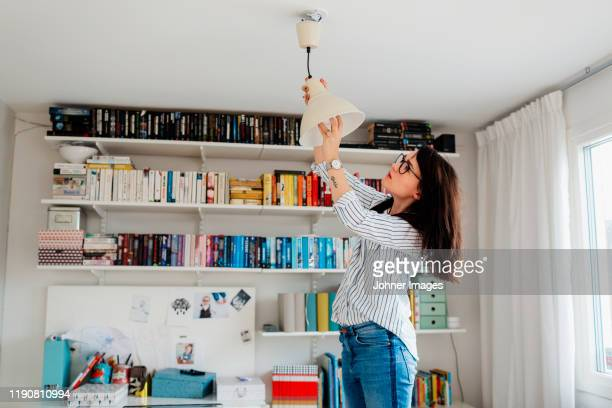 woman changing bulb in house - electric lamp stock pictures, royalty-free photos & images