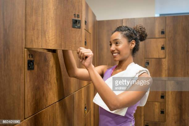 woman changing in the lockers room at the gym - locker room stock pictures, royalty-free photos & images