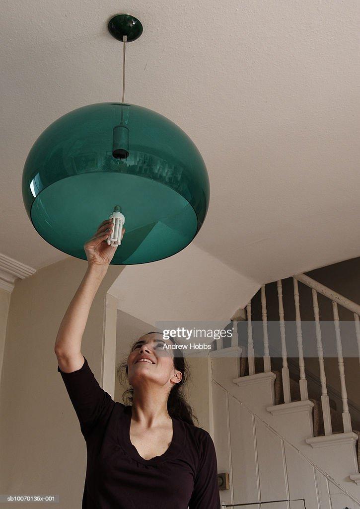 Woman changing lightbulb at home : Bildbanksbilder