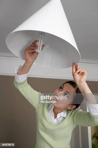 woman changing lightbulb - energy efficient lightbulb stock pictures, royalty-free photos & images