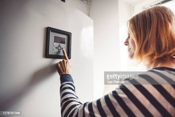 woman changing the settings on the boiler - boiler stock pictures, royalty-free photos & images