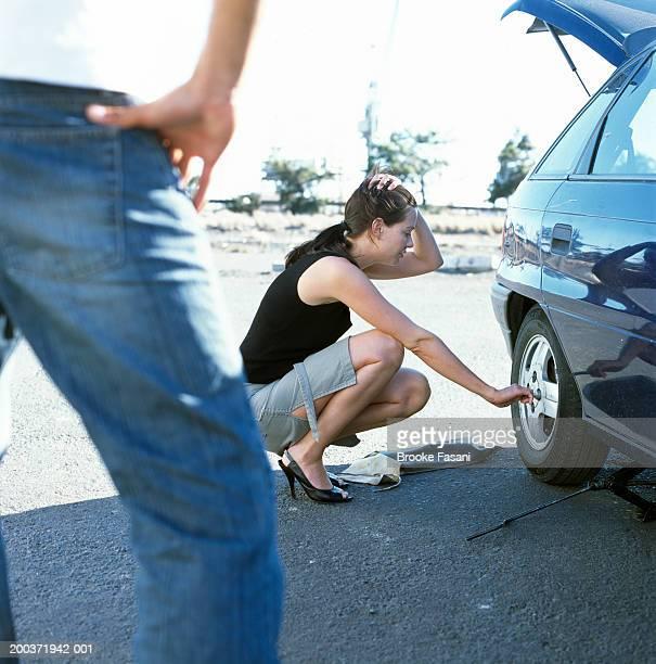 woman changing tire, man with hand on hips - partire bildbanksfoton och bilder