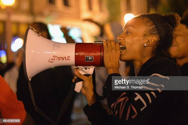 A woman chants through a megaphone during a protest action through the Central West End of St Louis Missouri on August 20 2015 After a night of...