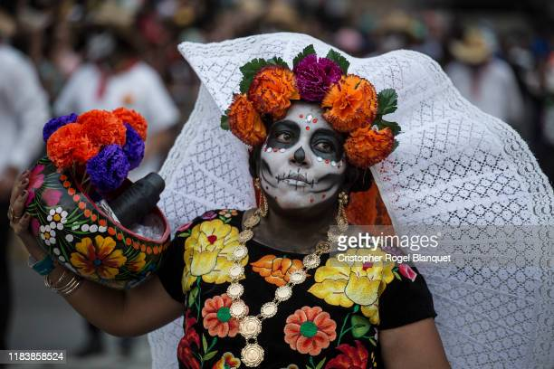 A woman characterized as Catrinas looks on during the Day of the Dead Parade in Mexico City on October 27 2019 in Mexico City Mexico Thousands of...