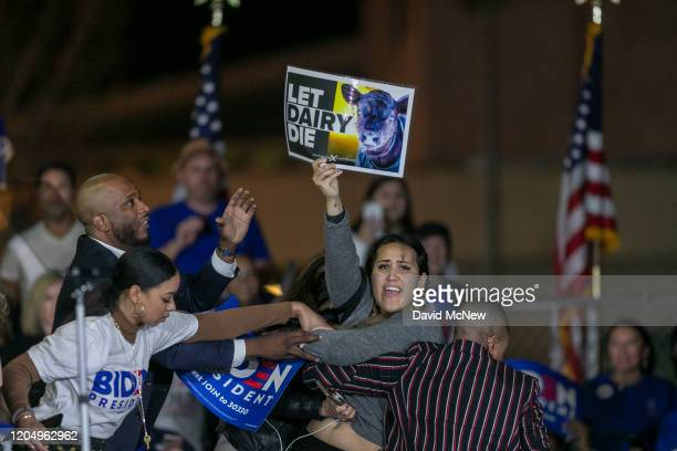 """Woman charges the stage while holding a sign that reads """"Let Dairy Die"""" as Democratic presidential candidate former Vice President Joe Biden speaks..."""