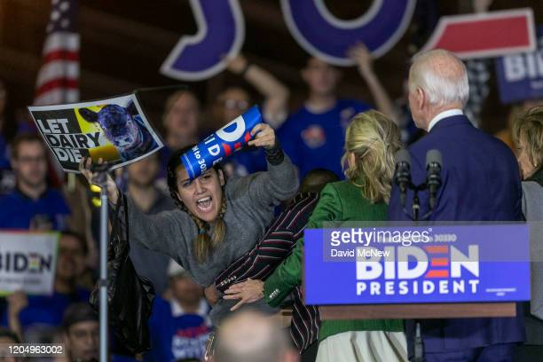 A woman charges the stage while holding a sign that reads Let Dairy Die as Democratic presidential candidate former Vice President Joe Biden speaks...