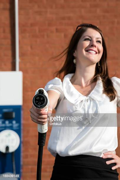 Woman Charging an Electric Vehicle at Charging Station