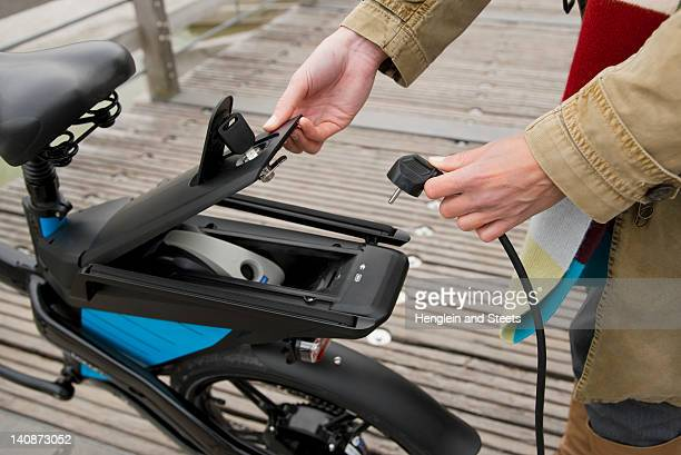 woman charging electric bike outdoors - charging sports stock photos and pictures