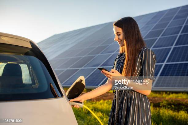 woman charging electric car and solar panels in background - station stock pictures, royalty-free photos & images
