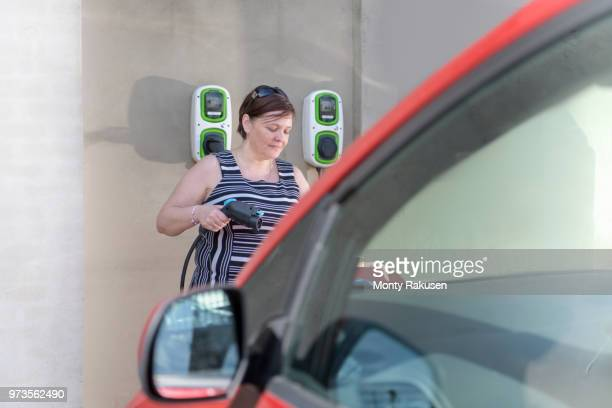 Woman charging electric car at city charging point